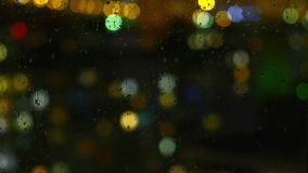 Rainy days, rain drops on window surface and colorful traffic bokeh light stock footage