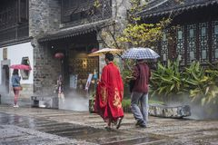 On rainy days, two tourists with umbrellas walked through the scenic spot, one of them wearing a red ancient robe. On rainy days, two tourists with umbrellas royalty free stock images
