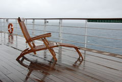 Rainy deckchair on Queen Mary 2. Teak steamer chairs on the deck of ocean liner Queen Mary 2 during heavy rain Royalty Free Stock Images
