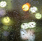 Rainy evening. Drops on glass. A luminescence of fires of a city life. Sight from within the car on a city, rainy evening Stock Images
