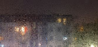 Rainy evening and the view of the rain-covered glass through which you can see a fuzzy block of flats. Rain, evening and the view of the rain-covered glass royalty free stock photos