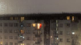 Rainy evening and the view of the rain-covered glass through which you can see a fuzzy block of flats. Rain, evening and the view of the rain-covered glass stock images