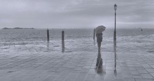 Rainy and fogy day in Venice with lonely woman with umbrella and moody seascape on backround. Italy stock photos