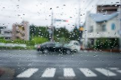 Rainy and gloomy day on the road with cars and traffic and rain is focused on the car`s windshield. royalty free stock photography