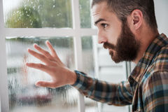 Rainy mood. Thoughtful young bearded man touching the window and looking through it stock image