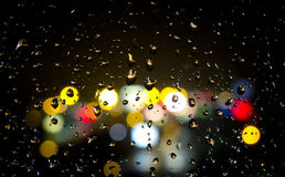 Rainy night. Street lights out of focus through rainy window pane with drops of water Royalty Free Stock Photography