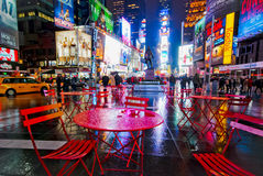 Rainy Night in the City. Rainy Times Square at night with colorful reflections and few figures with empty wet red tables. Iconic view of NYC