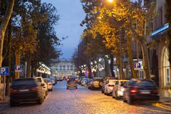 Rainy night in the parking shopping mall, the headlights of the cars. Night scene of city road in Kutaisi. Cars on the street. Christmas in Town Royalty Free Stock Photos