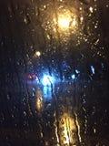 Rainy night. Rain stream on the car window Royalty Free Stock Photography