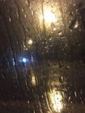 Rainy night. Rain stream on the car window Royalty Free Stock Images