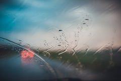 Rainy road through car window. Rainy road through the car window. Machinery lights ahead stock images