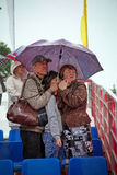 Rainy summer day. Torrential rain on the square during the festival, people hiding under umbrellas Stock Image