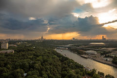 Rainy sunset clouds above river and a large city Stock Images