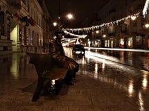 Rainy Tuwim. Monuments Bench Tuwim Piotrkowska Street in Lodz, in the scenery of street lights and heavy rain Royalty Free Stock Image