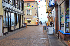 Rainy vacation street. A wet street at a holiday resort. looking down the almost deserted street past the ice cream parlor and the pub towards the railings by Royalty Free Stock Photo