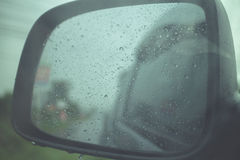 Rainy view in car side mirror Royalty Free Stock Images