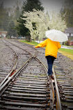 Rainy Walk on Tracks. An lady walking wet railroad tracks in the rain wearing a colorful yellow jacket and carrying an umbrella under dark skies.  Shallow depth Royalty Free Stock Photos