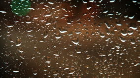 Rainy water drops on the car glass evening traffic view. Unfocused blured city traffic lights bokeh stock footage