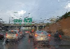 Rainy weather on the highway-traffic viewed through a car window. Highway Road view through car window blurry with heavy rain, Concept of driving in rain, bad Royalty Free Stock Images