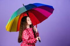 Rainy weather with proper garments. Bright umbrella. Be rainbow in someones cloud. Rainy day fun. Happy walk under. Umbrella. Enjoy rain concept. Kid girl happy royalty free stock photography