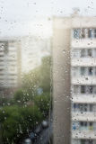 Rainy window Blurred building sky and cars Rainy weather Vertical photo Stock Photography