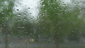 Rainy and windy weather during a hurricane and hail - View from a warm car through the windshield window with rain drops stock video