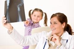 Raio X fêmea novo da mostra do doutor à criança Fotos de Stock