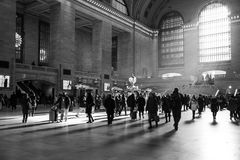 Raios de luz solar dentro da estação de Grand Central com os povos que andam no tempo da precipitação Fotografia de Stock Royalty Free