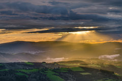 Raios de sol através das nuvens no por do sol Fotos de Stock Royalty Free