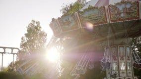 Raios de sol que brilham com o passeio do balanço no parque de diversões vídeos de arquivo