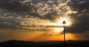 Raios de sol, vistos através de um cargo solitário da lâmpada, Sedella, Espanha Fotografia de Stock Royalty Free