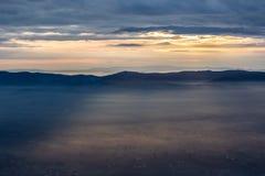 Raios de Sun que vêm para baixo de algumas nuvens sobre um vale enchido pela névoa, parte de iluminação dela fotos de stock