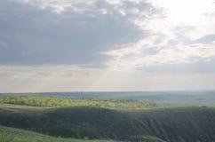 Raios do sol atrás de uma nebulosidade os prados e os campos Fotografia de Stock
