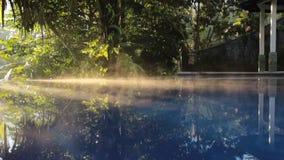 Raios do sol da manhã através do fumo acima da associação com água azul na floresta verde da selva filme