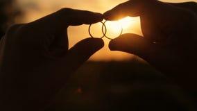 Raios do sol da noite através das alianças de casamento vídeos de arquivo