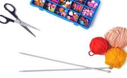 Rais pour tricoter, une boîte avec des accessoires et ciseaux sur un wh Images libres de droits