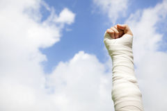 Raise bandaged arm  with blue sky background Royalty Free Stock Photo