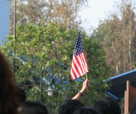 Raise the flag. Person raising the American Flag in a crowd Stock Image