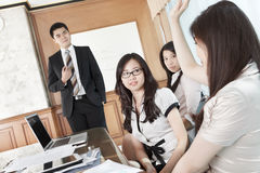 Raise hand in meeting. Businesswoman raise hand to ask the manager in a briefing stock photo