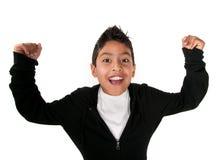 Raised Arms of Joy. Cute Latino boy smiles with raised arms Stock Photo