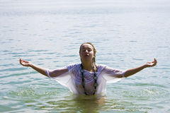 Raised arms in the water. Young blond woman meditating in the water Royalty Free Stock Photos