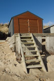 Raised beachhut. Beach-hut made of metal with wooden doors on a raised wooden platform with a ladder from the beach, a blue sky makes the back-drop Stock Photos