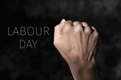 Raised fist and text labour day. Closeup of the raised fist of a young man against a gradient dark gray background and the text labour day Royalty Free Stock Photo