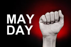 Raised fist and text may day. Closeup of the raised fist of a young caucasian man and the text may day on a red background Stock Photo