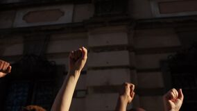 Raised fists against the backdrop of a city wall. People are chanting slogans. The protest against racism. Protests in