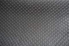 Raised geometric pattern on black polyester. Fabric Stock Image