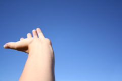 Raised Hand. Woman's hand raised against the blue sky. Lots of room for added images or copy Stock Photo