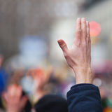 Raised hand. In a crowd of people Royalty Free Stock Photos