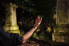 Raised hand by grave Royalty Free Stock Images
