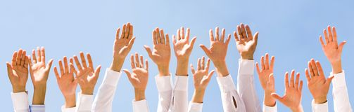Raised hands. Close-up of several human hands raised against cloudy sky Stock Photos
